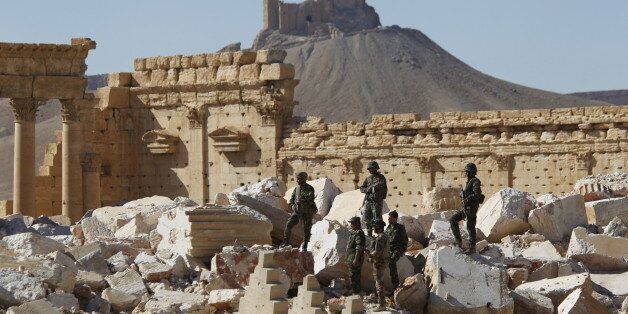 Syrian army soldiers stands on the ruins of the Temple of Bel in the historic city of Palmyra, in Homs...