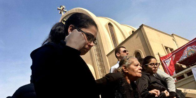 Coptic Christian woman leave after a funeral service for victims of a Sunday cathedral bombing, at the...