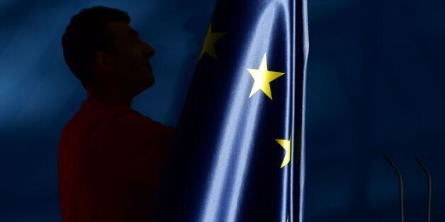The flags, including the EU flag, are taken down after a press conference at the chancellery in Berlin,...
