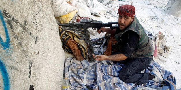 A Free Syrian Army fighter gestures during a fight with forces loyal to Syrian President Bashar Al-Assad...