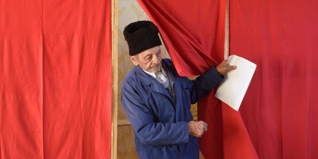 An elderly man leaves a polling booth to cast his ballot at a polling station in the village of Singureni,...