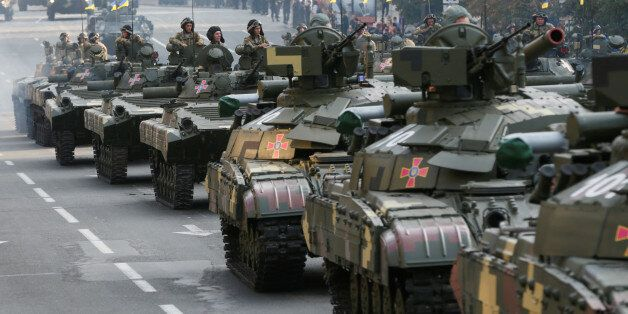 Ukrainian servicemen sit atop tanks and infantry fighting vehicles before a rehearsal for the Independence...
