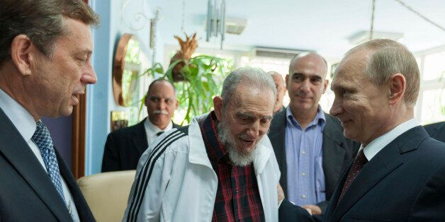 Cuba's former President Fidel Castro (C) talks with Russia's President Vladimir Putin (R) during a meeting...