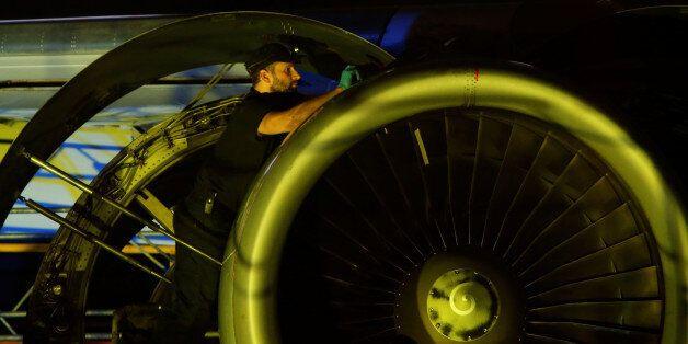 An aircraft technician carries out maintenance on the engine of an airplane inside a Lufthansa Technik...