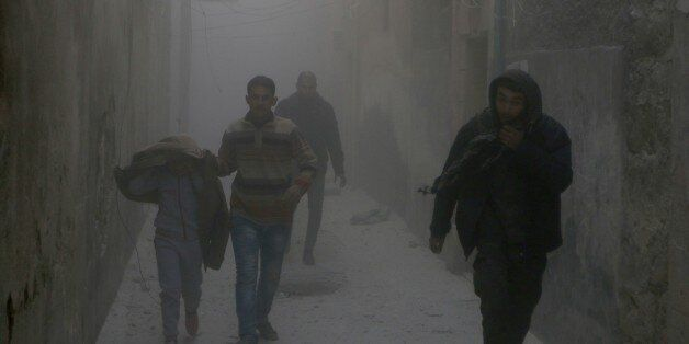ALEPPO, SYRIA - NOVEMBER 21: Residents escape from the scene of the air strikes carried out by the war...