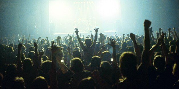 A general view of a rock concert taken from the back fo a venue showing the audience in silhouette raising...