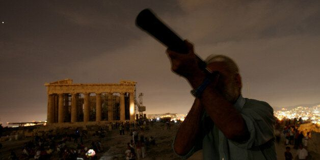 A Greek man looks through his telescope at the full moon as at the backround is seen the ancient temple...
