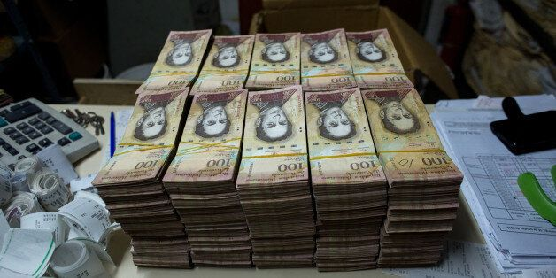 Stacks of banknotes sit on a desk inside the office of a bakery in Caracas, Venezuela, on Sunday, Oct....