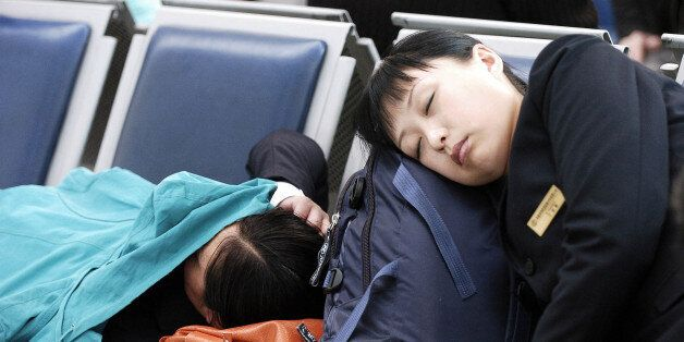 In this photo released by China's official Xinhua news agency, passengers fall asleep while waiting for...