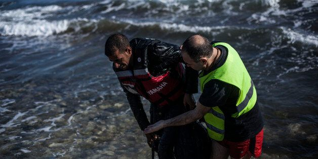 A volunteer, right, helps a Syrian refugee to get out of the sea after his arrival on the Greek northeastern...