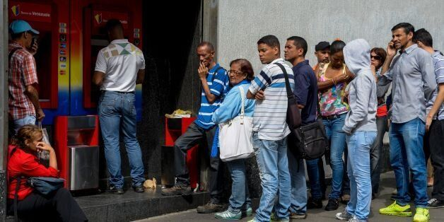 People queue to withdraw money from an automated teller machine (ATM) in Caracas on December 1, 2016.Venezuelan...
