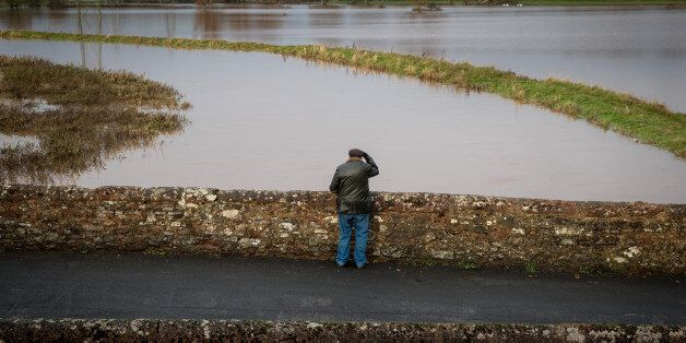 EXETER, ENGLAND - NOVEMBER 22: A man looks at flood water in fields surrounding the village of Clyst...