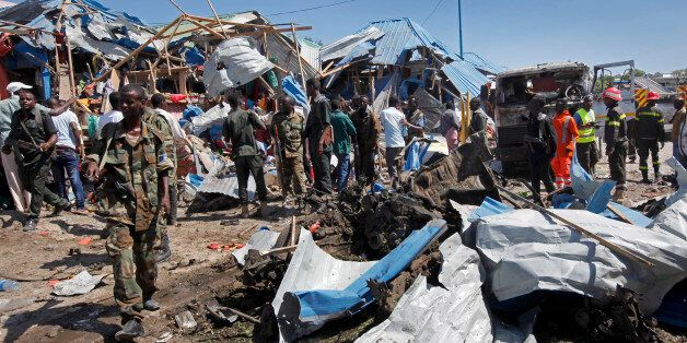 Somali soldiers walk through the wreckage after a car bomb that targeted a police station in the Waberi...