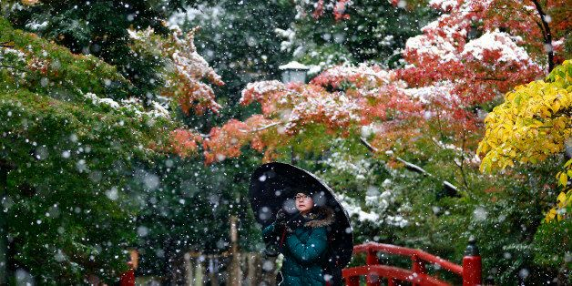 A visitor takes a photo in the snow at the Tsurugaoka Hachimangu Shrine in Kamakura, near Tokyo, Thursday,...