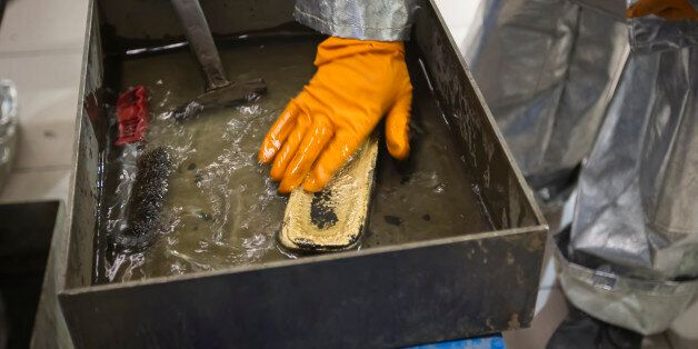 A worker cleans just melted gold alloy bar in a workshop of Altyntau gold mine extraction factory outside...