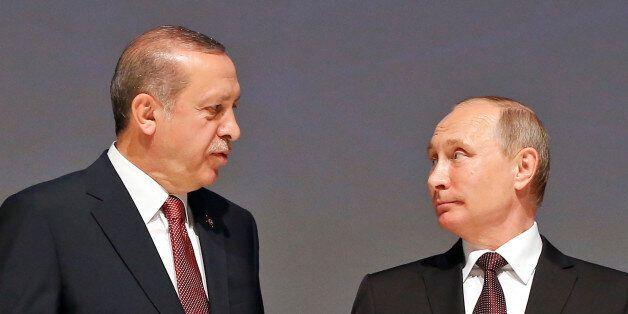 Turkey's President Recep Tayyip Erdogan, left, talks to Russian President Vladimir Putin, right, as they...