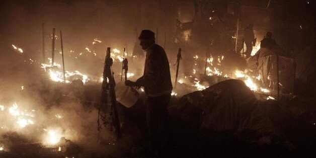 People try to extinguish fires with buckets at the moria migrants camp on the island of Lesbos early...