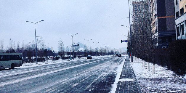 Snow Covered Street By Buildings Against Sky During