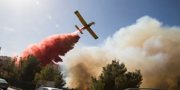 An Israeli firefighter plane helps extinguish a bushfire in the northern Israeli port city of Haifa on...