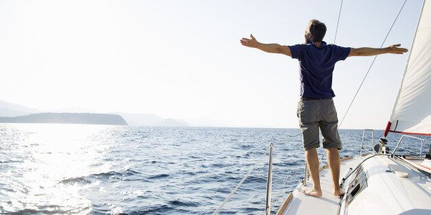 man stands at bow of yacht with arms