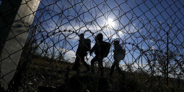 Migrants walk along Hungary's border fence on the Serbian side of the border near Morahalom, Hungary,...
