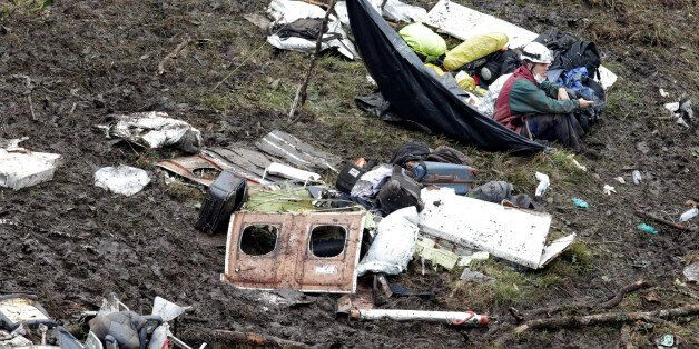 A rescue worker sits near the wreckage of a plane that crashed into the Colombian jungle with Brazilian...