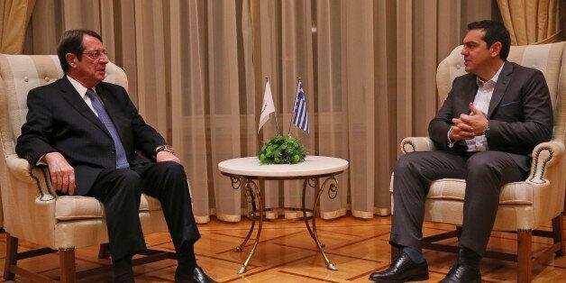 Greek Prime Minister Alexis Tsipras, right, talks with Cyprus' President Nicos Anastasiades, during their...