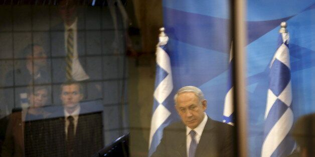 A reflection of Israeli Prime Minister Benjamin Netanyahu (C) is seen as he delivers a joint statement...