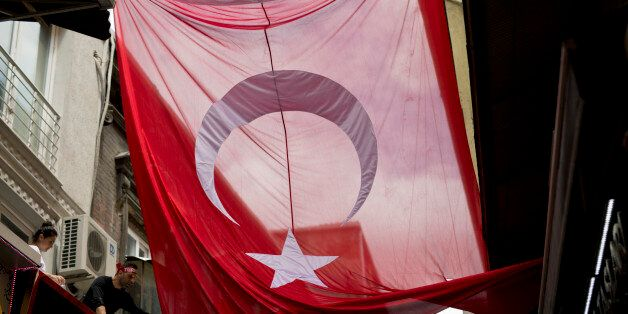 A man tries to unwrap a giant Turkish flag at Grand bazaar, one of the largest and oldest covered markets...