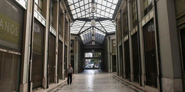 A pedestrian walks past closed and shuttered shops inside a shopping arcade in Athens, Greece, on Sunday,...