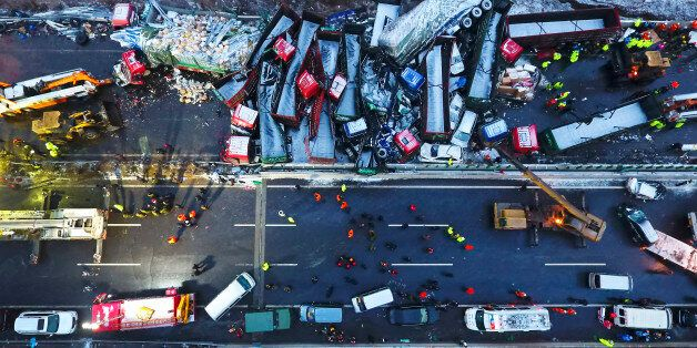 In this Monday, Nov. 21, 2016 photo released by Xinhua News Agency, rescuers work near vehicles collided...