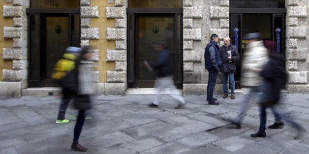 People walk in front of the Monte dei Paschi bank in Siena, central Italy, January 29, 2016. Merger talks...