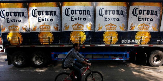 A man cycles past a truck of Corona beer produced by Group Modelo in Mexico City July 16, 2013. After...