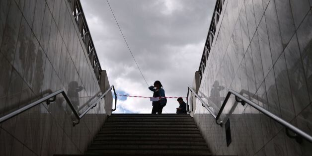 A woman reads an announcement informing about a 48-hours strike as she stands at a closed metro station...