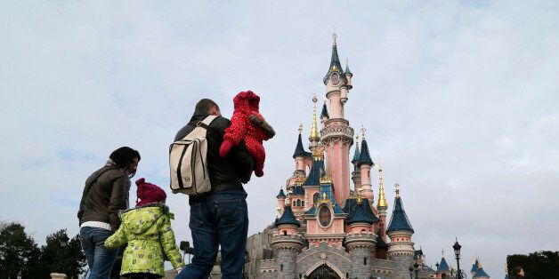 Visitors walk towards the Sleeping Beauty Castle during a visit to the Disneyland Paris Resort run by...