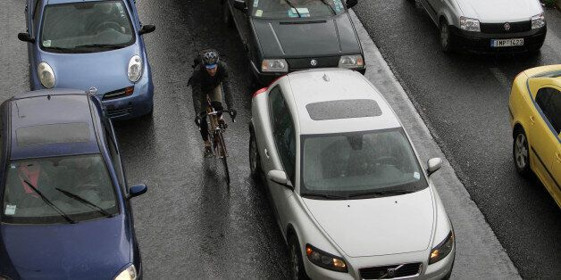 Cars caught in a traffic jam as a cyclist passes among them during a 24-hour strike held by metro, tram...