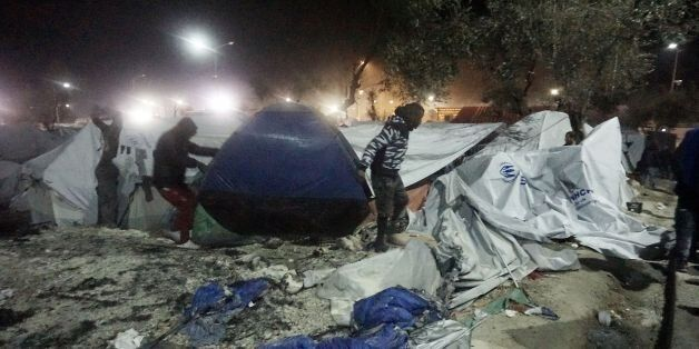 Migrants move their tent following an explosion and fire at a migrant camp on the island of Lesbos early...