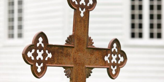 Rusted cemetery cross and white wooden church out of focus.