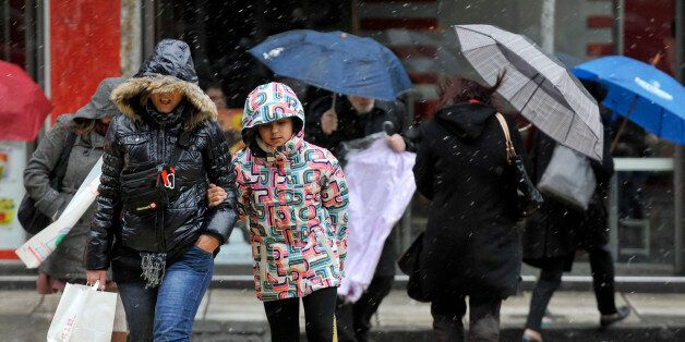 Pedestrians walk during a snowfall in the central of the northern Greek port city of Thessaloniki, Thursday,...
