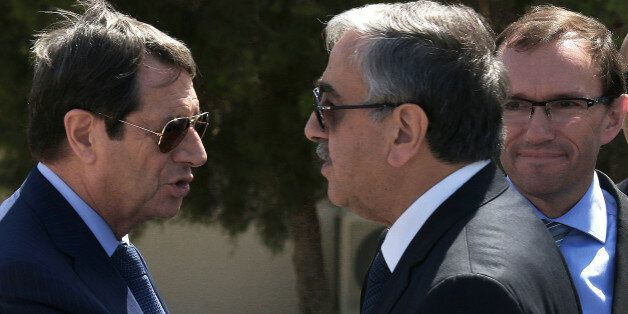 Cypriot President Nicos Anastasiades, left, breakaway Turkish Cypriot leader Mustafa Akinci, right, talks...
