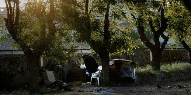 A homeless woman is seen near her belongings in central Athens, early Wednesday, May 13, 2015. Greece,...