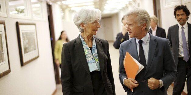 International Monetary Fund (IMF) Managing Director Christine Lagarde (C) speaks with IMF Director of...