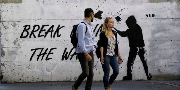 A couple walk in front of a wall with graffiti, near the UN buffer