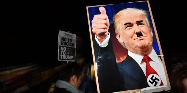 TOPSHOT - A demonstrator holds a placard showing a picture of US President-elect Donald Trump modified...