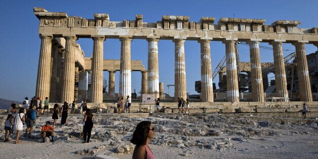Tourists stand in front of the Parthenon temple as they visit the archaeological site of the Acropolis...