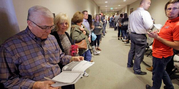 Frank Medina, left, reads the voter information pamphlet as he waits in line to vote at the Holladay...
