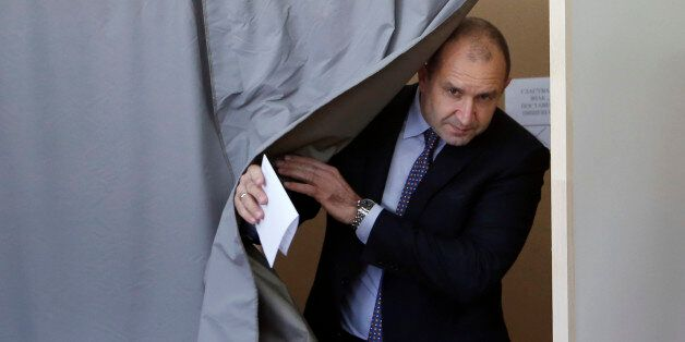 Bulgarian Socialists Party candidate Rumen Radev comes out from the polling booth at a polling station...