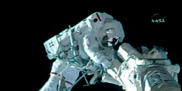 Astronaut Shane Kimbrough, attached to a work platform on the end of the Space Shuttle Endeavour's robotic...