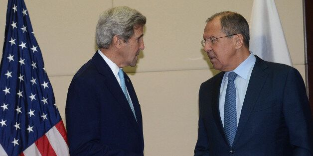 US Secretary of State John Kerry (L) speaks with Russia's Foreign Minister Sergey Lavrov as they meet...