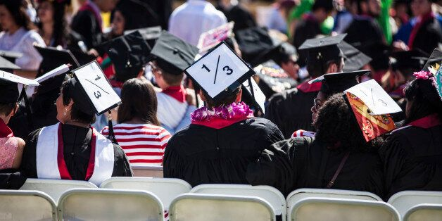 STANFORD, CA - JUNE 12: Graduating students wear signs on their caps, a reference to rape statistics,...